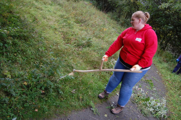 Volunteer from People's Postcode Lottery scything the meadow at Jupiter Urban Wildlife Centre © Rory Syme