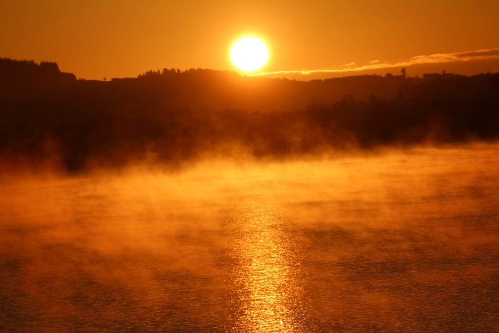 Golden sunrise over the misty Loch